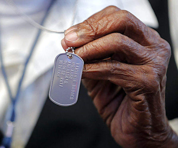 World War II veteran Lawrence Brooks holds a dog tag honoring him as the oldest living World War II veteran, as he celebrates his 110th birthday at the National World War II Museum in New Orleans, Thursday, Sept. 12, 2019. Brooks was born Sept. 12, 1909, and served in the predominantly African-American 91st Engineer Battalion, which was stationed in New Guinea and then the Philippines during World War II. He was a servant to three white officers in his battalion. (AP Photo/Gerald Herbert)